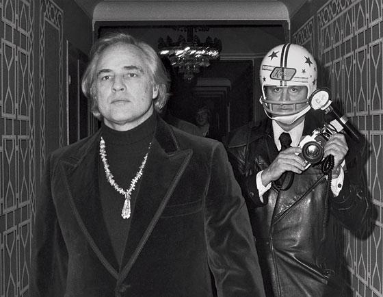 Marlon Brando seguito da Ron Galella protetto da un casco (1974)